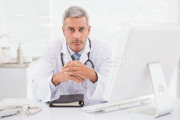 Unsmiling doctor looking at camera  Stock photo © wavebreak_media