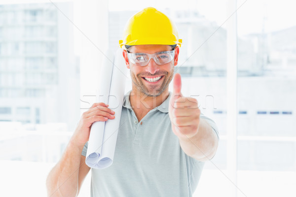 Happy handyman with rolled up blueprint gesturing thumbs up Stock photo © wavebreak_media