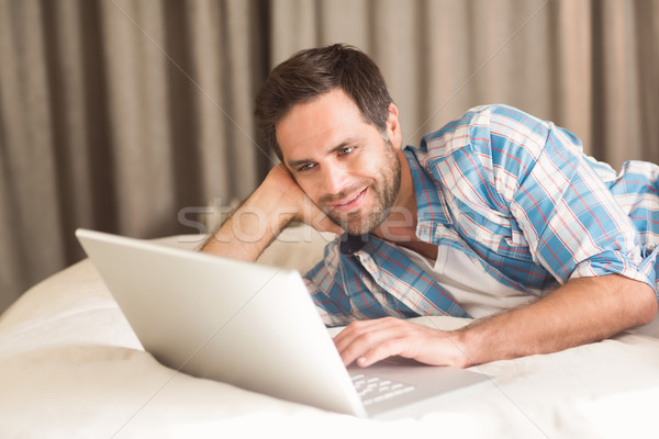Handsome man relaxing on his bed with laptop Stock photo © wavebreak_media