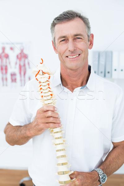 Smiling doctor showing anatomical spine Stock photo © wavebreak_media