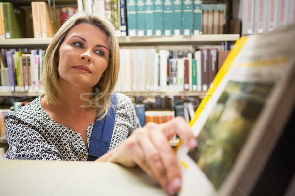 Mature student picking out book in library Stock photo © wavebreak_media