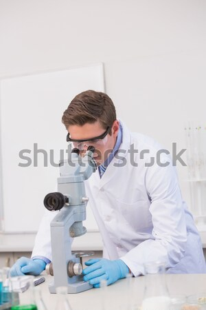 Scientist examining sample with microscope  Stock photo © wavebreak_media