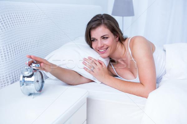 Happy brunette extending hand to alarm to clock in bed  Stock photo © wavebreak_media