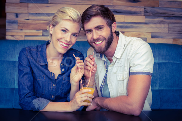 Cute couple on a date sharing a glass of orange juice Stock photo © wavebreak_media