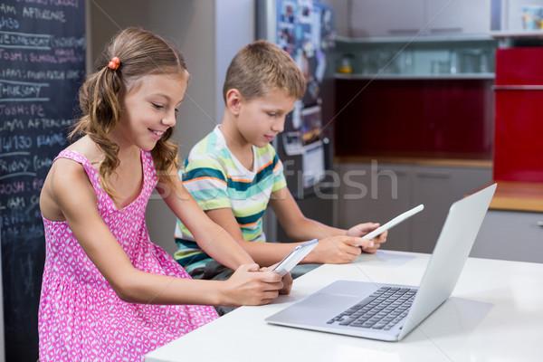 Irmãos digital comprimido telefone móvel cozinha casa Foto stock © wavebreak_media