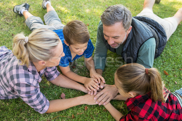 Family lying and putting their hands together in park Stock photo © wavebreak_media