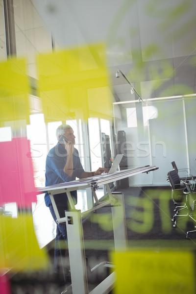 Mature businessman seen through glass in office Stock photo © wavebreak_media