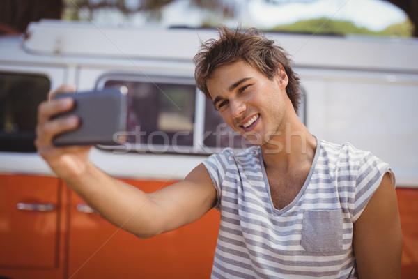 Young man clicking selfie while standing against van Stock photo © wavebreak_media