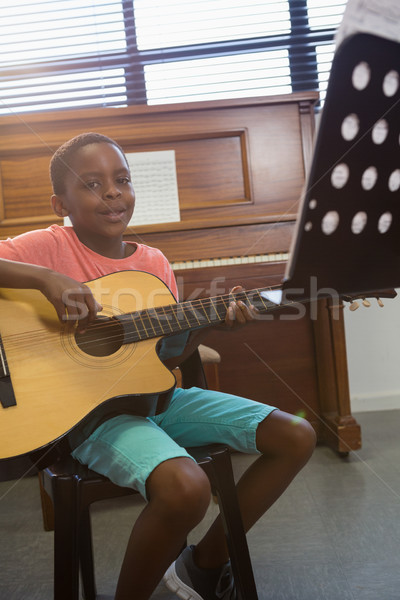 Portrait of boy playing guitar while sitting in classroom Stock photo © wavebreak_media