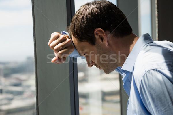 Depressed male executive leaning on window glass Stock photo © wavebreak_media