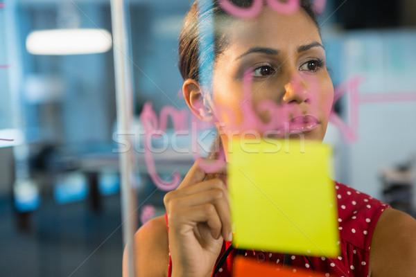 Thoughtful female executive looking at sticky notes Stock photo © wavebreak_media