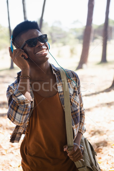 Moço óculos de sol fones de ouvido ouvir música parque arte Foto stock © wavebreak_media