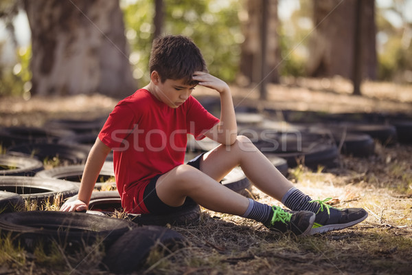 Sad boy relaxing on tyre during obstacle course Stock photo © wavebreak_media