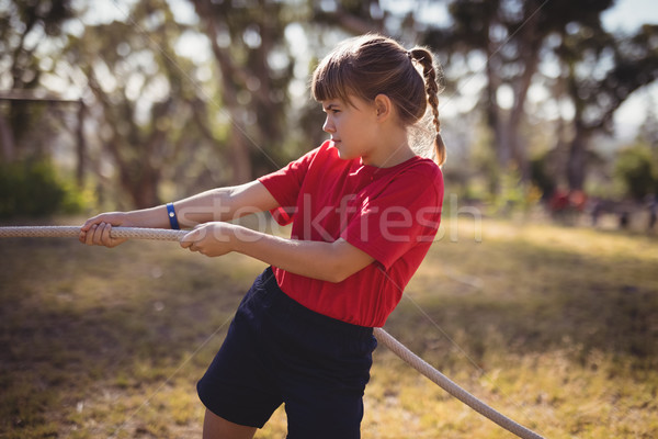 Determined girl practicing tug of war during obstacle course Stock photo © wavebreak_media