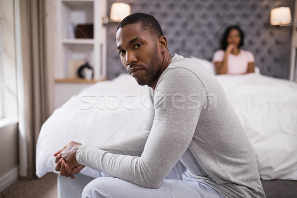 Young man siting while woman resting on bed at home Stock photo © wavebreak_media