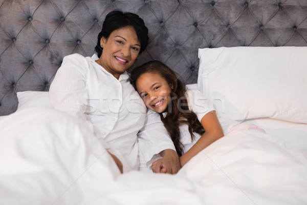 Smiling grandmother and granddaughter relaxing on bed at home Stock photo © wavebreak_media