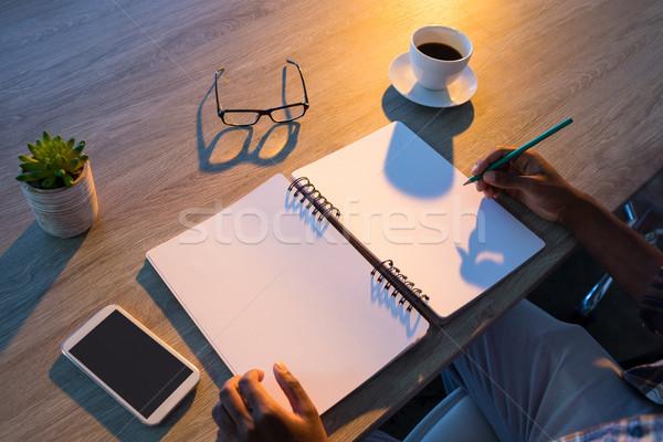 Male executive writing in diary at his desk Stock photo © wavebreak_media