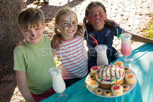 Happy friends with face paint sitting by food and drink at table Stock photo © wavebreak_media