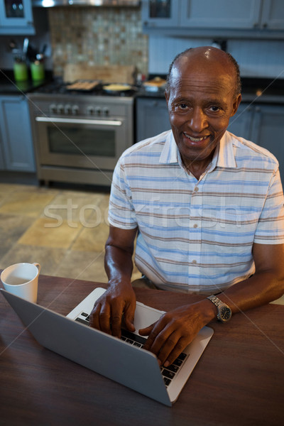 High angle view smiling senior man using laptop Stock photo © wavebreak_media