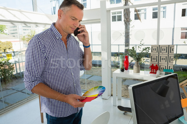Businessman holding color swatch while talking on mobile phone Stock photo © wavebreak_media