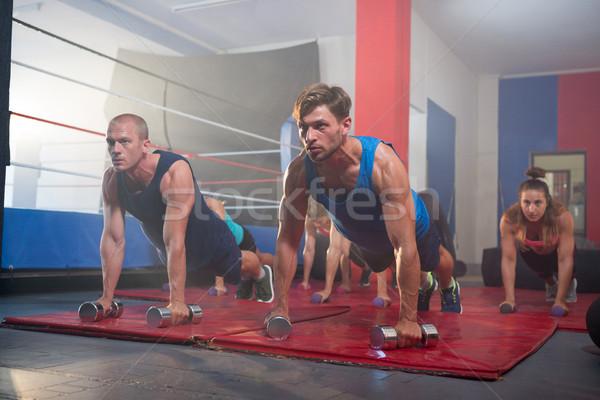 Fiatal sportolók gyakorol fekvőtámaszok súlyzók box Stock fotó © wavebreak_media