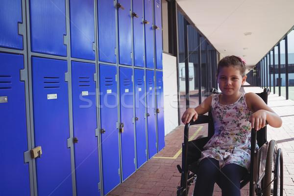 Portrait of schoolgirl sitting on wheelchair by lockers Stock photo © wavebreak_media