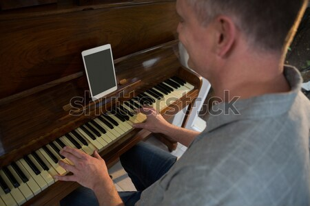 Elementary girl looking at digital tablet on stand while practicing piano Stock photo © wavebreak_media
