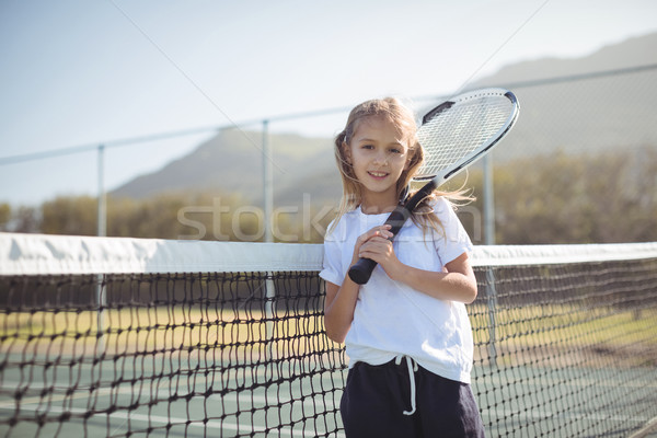 Smiling girl holding tennis racket while standing by net Stock photo © wavebreak_media