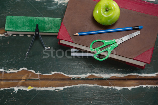 Various stationery with books and apple on wooden table Stock photo © wavebreak_media