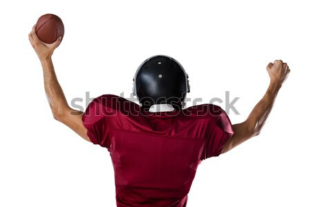 Rear view of sportsman holding football with arms raised Stock photo © wavebreak_media