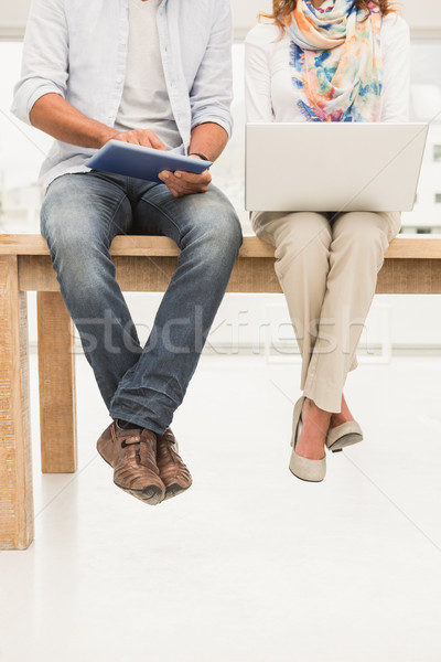 Casual designers sitting on wooden desk and using devices Stock photo © wavebreak_media