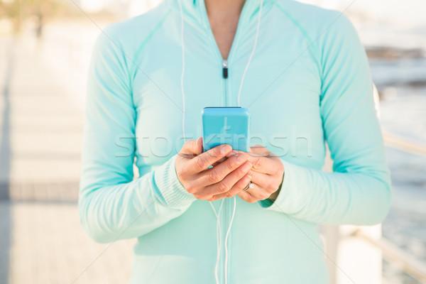 Geschikt vrouw luisteren naar muziek telefoon promenade Stockfoto © wavebreak_media