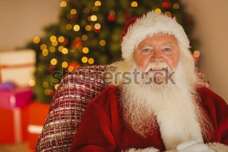 Santa Claus having a cookie with milk Stock photo © wavebreak_media