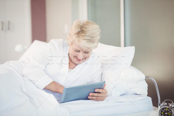 Senior woman using digital tablet while resting on bed Stock photo © wavebreak_media