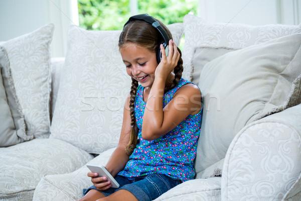 Dziewczyna telefonu słuchanie muzyki sofa wesoły Zdjęcia stock © wavebreak_media