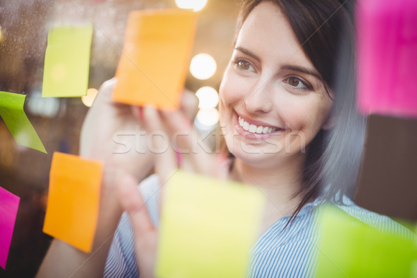 Creative businesswoman writing on sticky notes Stock photo © wavebreak_media