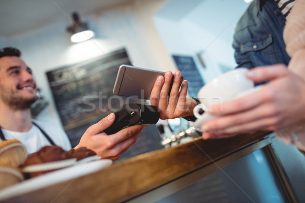 Customer with cellphone standing with barista at cafe Stock photo © wavebreak_media