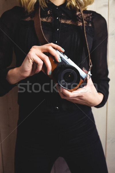 Mid-section of woman standing with camera Stock photo © wavebreak_media