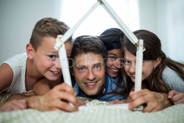 Happy family playing with model house in bedroom Stock photo © wavebreak_media