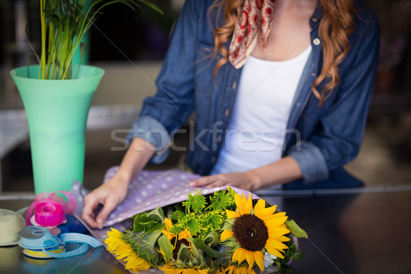 Female florist wrapping flower bouquet Stock photo © wavebreak_media