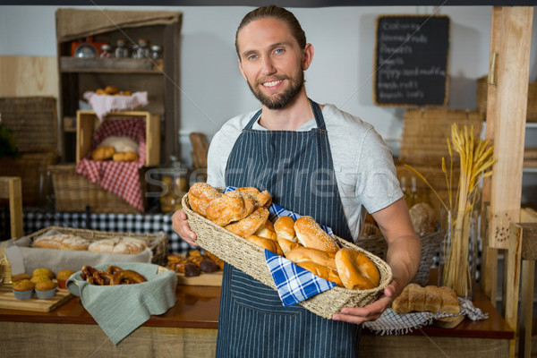 Smiling male staff holding wicker basket of various breads at counter Stock photo © wavebreak_media