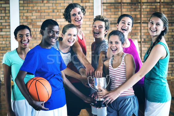 Smiling high school kids holding trophy in basketball court Stock photo © wavebreak_media