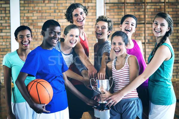 Lächelnd High School Kinder halten Trophäe Basketballplatz Stock foto © wavebreak_media