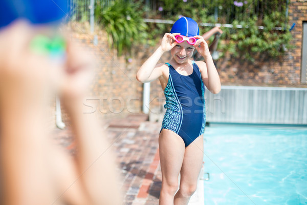 Little girl wearing swimming goggle at poolside Stock photo © wavebreak_media