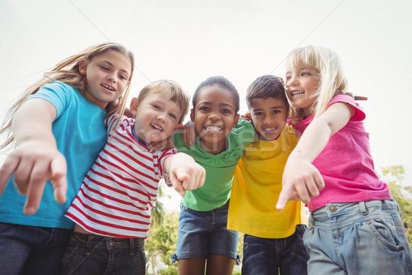 Mosolyog osztálytársak mutat kamerába fű gyermek Stock fotó © wavebreak_media