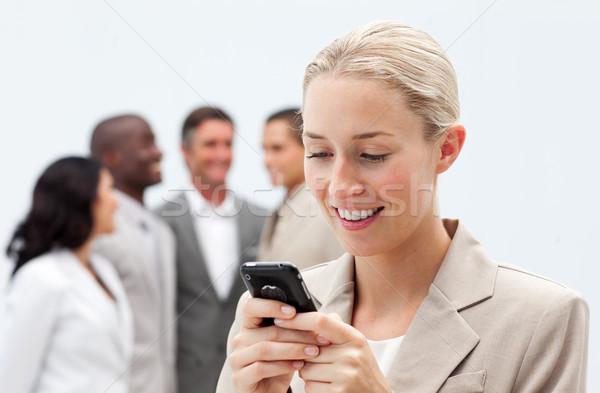 Lächelnd Geschäftsfrau Text Handy Arbeitsplatz Stock foto © wavebreak_media