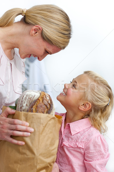 Smiling mother and her daughter unpacking grocery bag  Stock photo © wavebreak_media