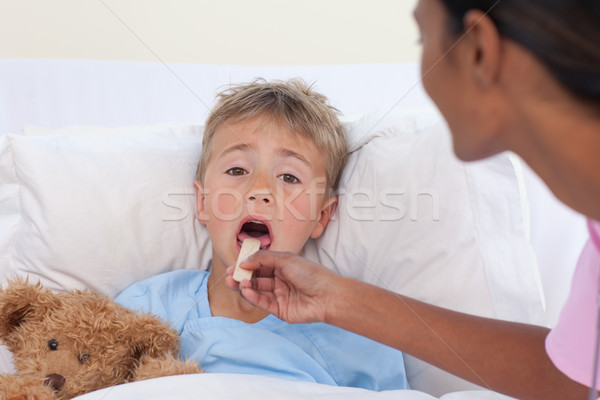 Nurse checking little boy throat in hospital Stock photo © wavebreak_media