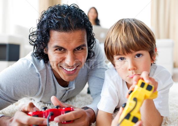 Happy father and his son playing video games lying on the floor Stock photo © wavebreak_media
