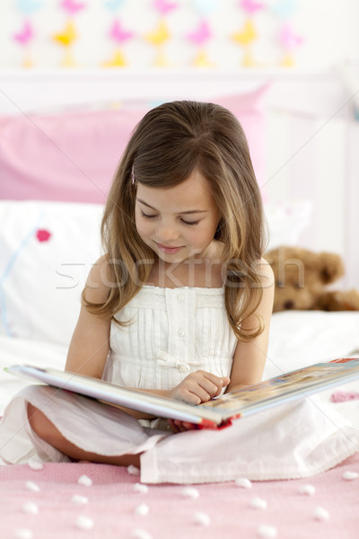Little girl sitting on bed reading a book Stock photo © wavebreak_media